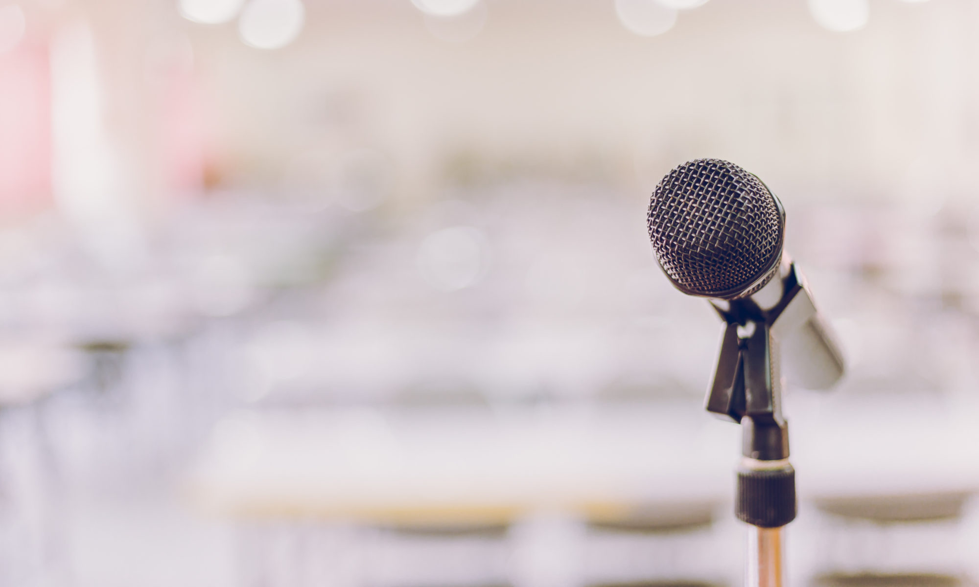 Microphone in focus at front of room